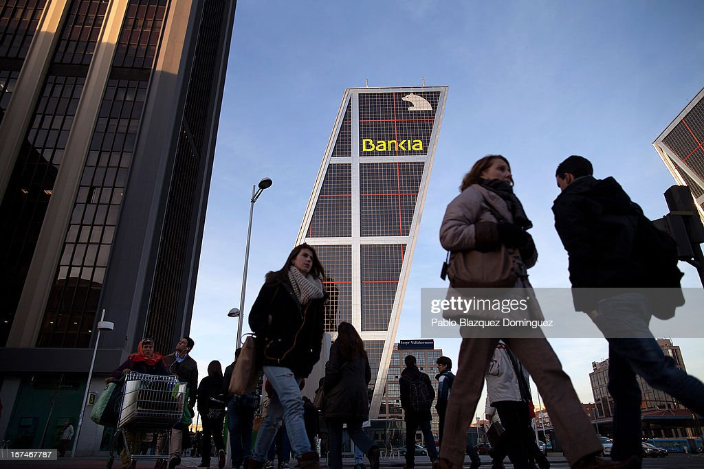 A woman pushes a trolley amid other pedestrains near the Bankia building at Plaza de Castilla on December 3, 2012 in Madrid, Spain. Spain has formally requested 39.5 euro billions bank bail-out of European funds. Economy Ministry of Spain, Luis de Guindos said that 37 euro billions will be paid for the four nationalized banks Bankia, Catalunya Banc, NCG Banco and Banco de Valencia while 2.5 euro billions will be for the 'bad banks'.