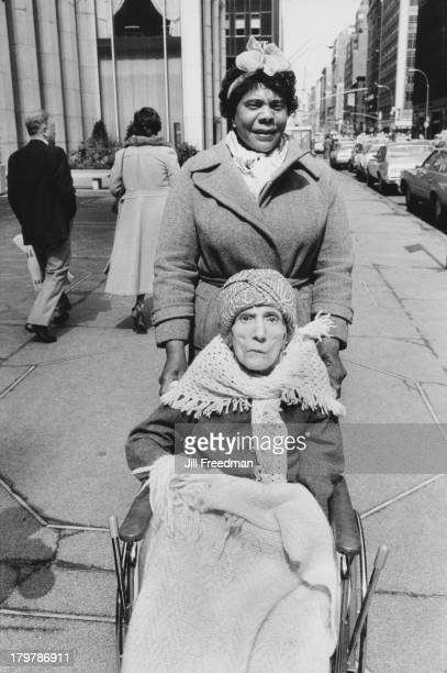 A woman pushes an elderly woman in a wheelchair in Midtown Manhattan New York City 1982