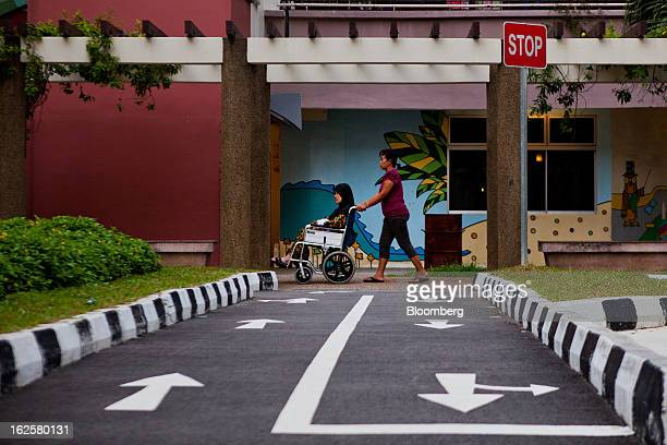 A woman pushes an elderly woman in a wheelchair through a public housing estate in Singapore on Sunday Feb 24 2013 Singapore's Finance Minister...