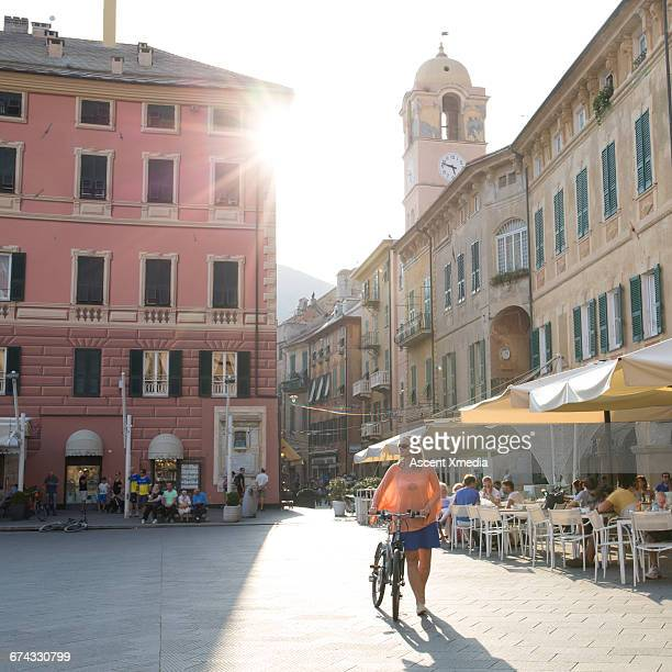 Woman pushes bike through town piazza, sunrise