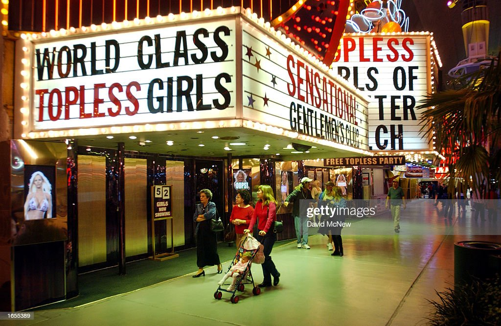 Viva Las Vegas. A Woman Pushes Her Baby Stroller Past A Topless Dance Club  On Fremont Street On November