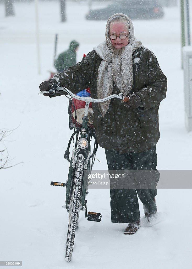A woman pushes her bicycle across a snow-covered sidwalk during a heavy snowfall in Zehlendorf district on December 9, 2012 in Berlin, Germany. Northeastern Germany was inundated with snow that covered highways and blanketed the region.