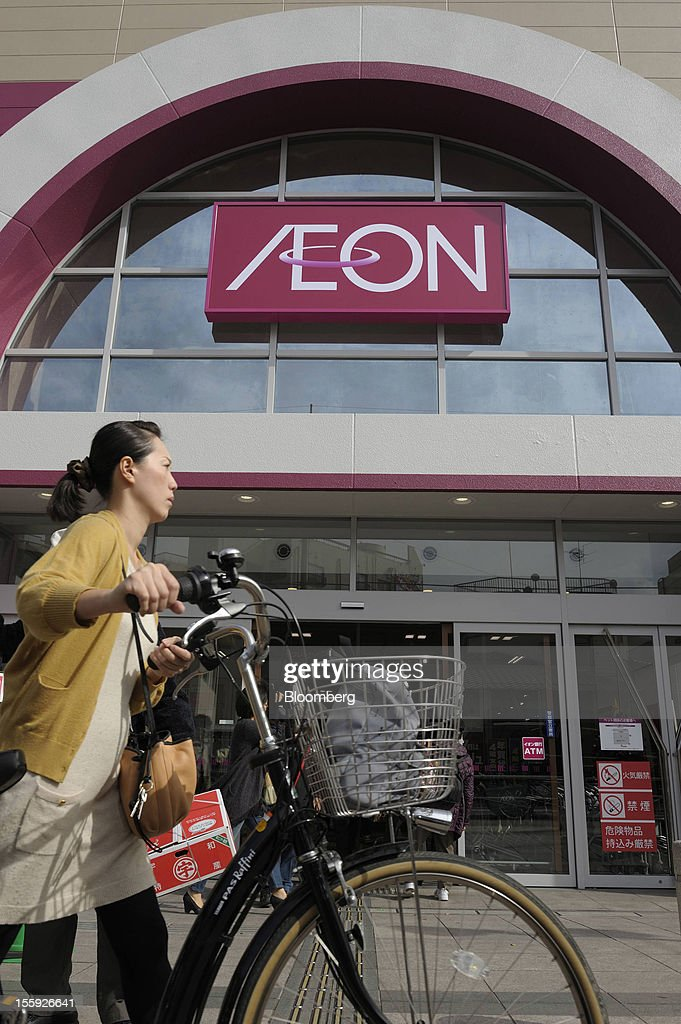 A woman pushes her bicycle past an Aeon Co. shopping center in Tokyo, Japan, on Friday, Nov. 9, 2012. Aeon Co. is Japan's largest supermarket operator. Photographer: Akio Kon/Bloomberg via Getty Images