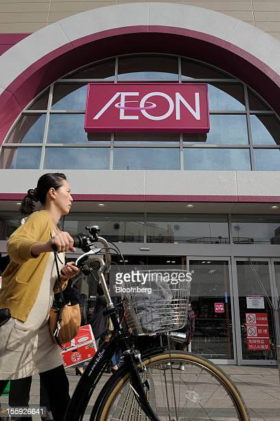 A woman pushes her bicycle past an Aeon Co shopping center in Tokyo Japan on Friday Nov 9 2012 Aeon Co is Japan's largest supermarket operator...