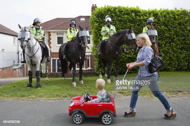 A woman pushes her child in a toy car past mounted police as protestors take part in a demonstration against the 2014 NATO Summit in Newport Wales on...