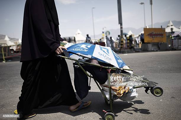 A woman pushes her child in a trolley to the pillars where pilgrims throw stone on the 2nd day of the 'Jamarat' ritual the stoning of Satan in Mina...