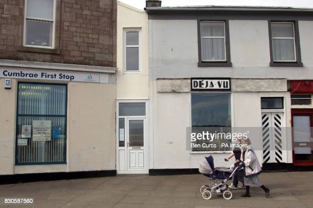 A woman pushes her pram past a house in Millport on Great Cumbrae Island Ayrshire known locally as 'The Wedge' which has gone on sale for 27000 and...