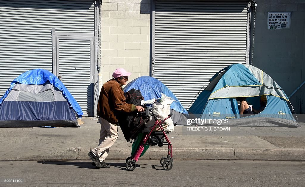 A woman pushes her walker past tents housing the homeless in Los Angeles, California on February 9, 2016. Los Angeles City and County officials are voting February 9 on plans aimed at ending homelessness in the community, mostly by making permanent housing available to the tens of thousands of people who are homeless. Frederic J. BROWN