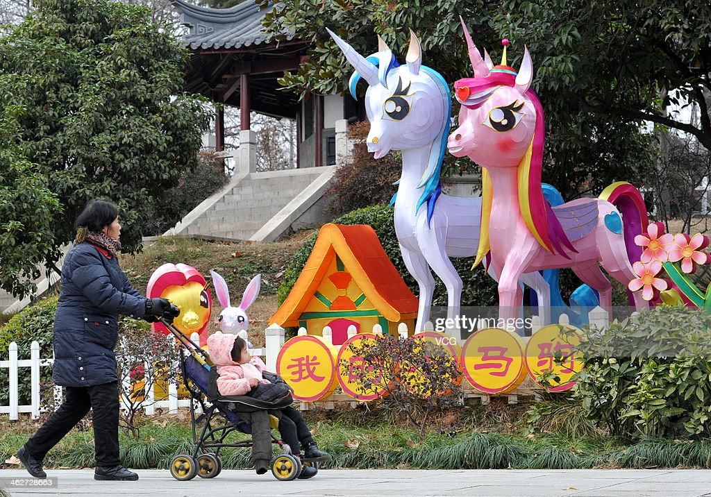 A woman pushing a baby walk past a horse decoration on January 13, 2014 in UNSPECIFIED, China. Chinese people are preparing for the Spring Festival, the year of horse, which will fall on January 31 according to Chinese calendar.