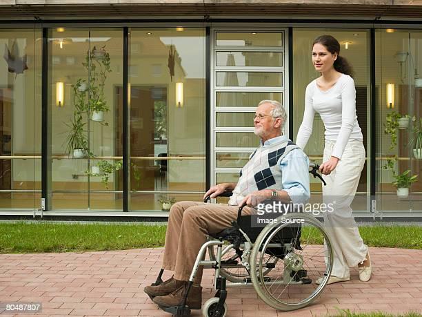 Frau Schieben ein Mann im Rollstuhl
