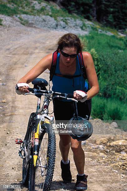 Woman pushing bicycle uphill, CO