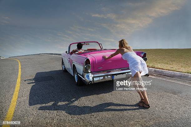 Woman pushing Convertible on road