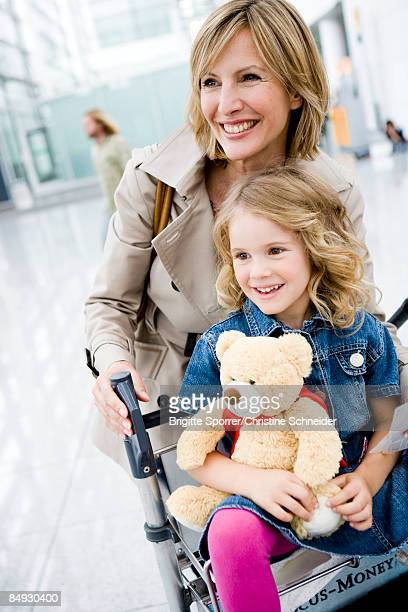 Woman pushing girl riding cart