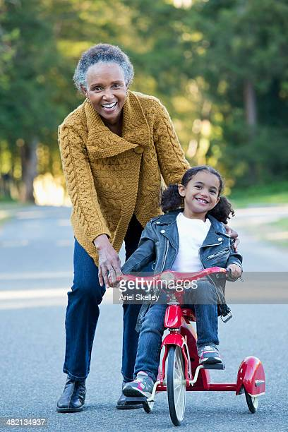 Woman pushing granddaughter on tricycle outdoors