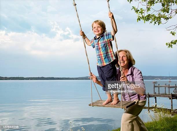 Woman pushing grandson on swing