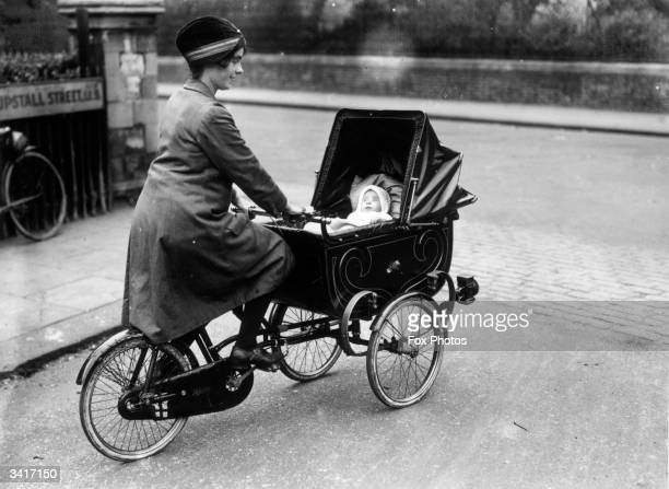 A woman pushing her baby in a specially adapted pram attached to her bicycle in Brixton south London