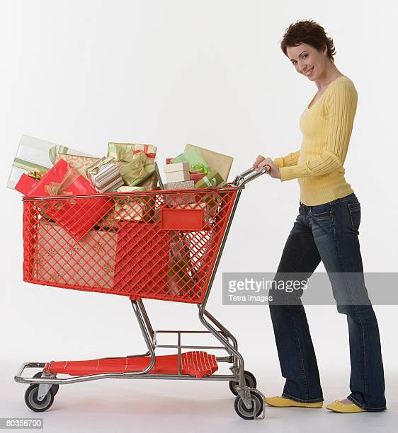 Woman pushing shopping cart of gifts