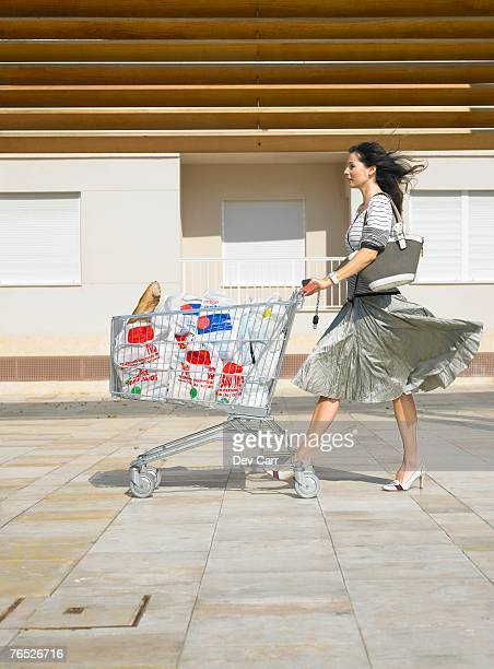 Woman pushing supermarket trolley against wind, Alicante, Spain,