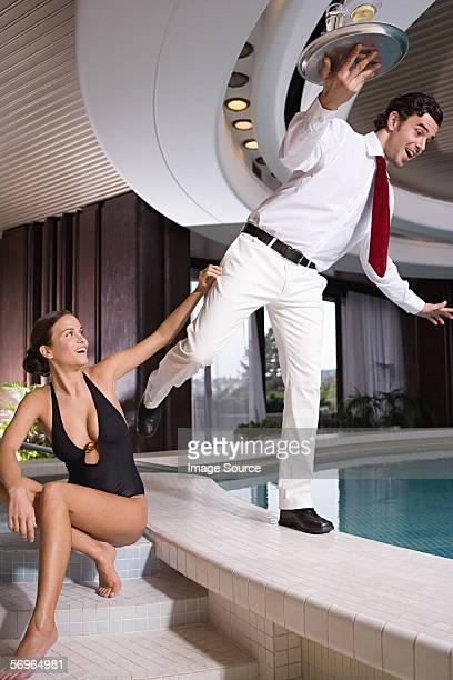 Woman pushing waiter into swimming pool