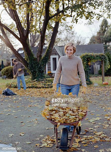 Woman pushing wheel barrow filled with leaves, smiling, portrait