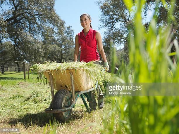 Woman pushing wheelbarrow full of hay