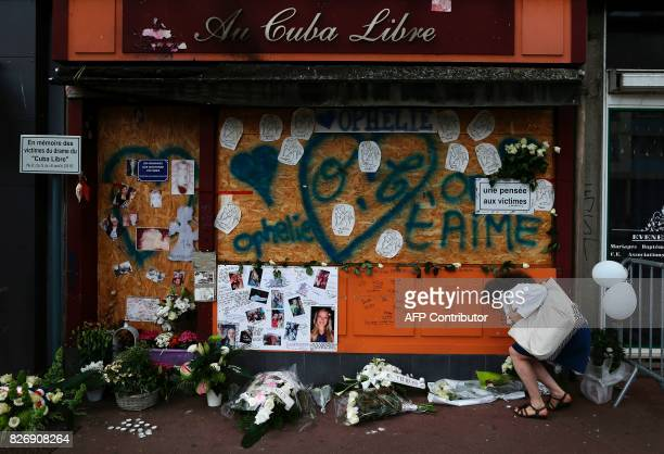 A woman put flowers at a makeshift memorial in front of the 'Au Cuba Libre' bar on August 6 in Rouen northwestern France in tribute to the 14 victims...