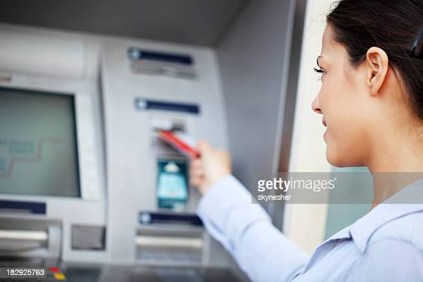 Woman put her credit card at the ATM.
