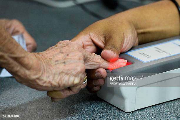A woman puts a finger on a fingerprint scanner during the authentication procedure of her signature for a recall referendum before the National...
