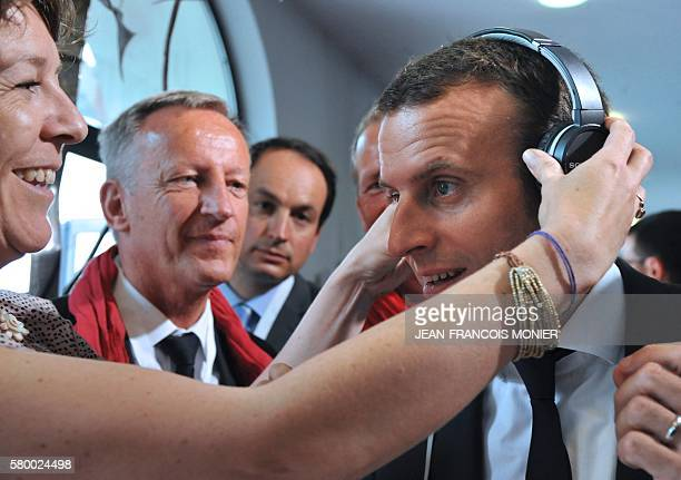 A woman puts a headset on the ears of French Economy and Industry minister Emmanuel Macron as he visits a virtual reality show on July 25 at the...