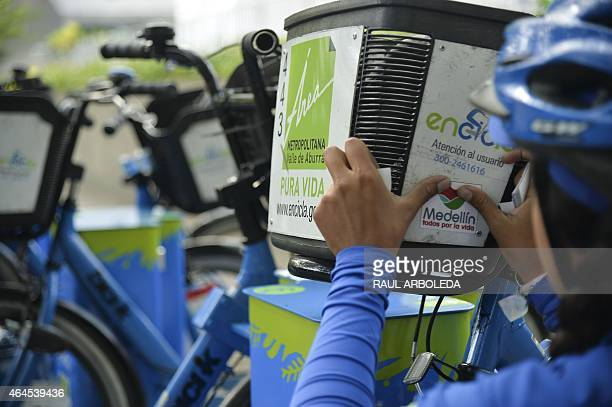 A woman puts a stickers on her bicycle during the 4th Annual World Bicycle Forum which theme is 'Cities for All in Medelin Antioquia department...