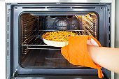 Close up of woman putting apple pie inside oven with gloves in her hand