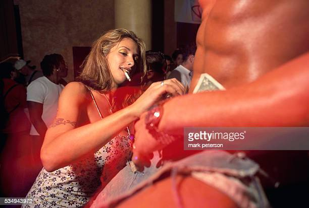 A woman puts dollar bills into a male stripper's shorts during Subliminal Sessions at CentroFly nightclub