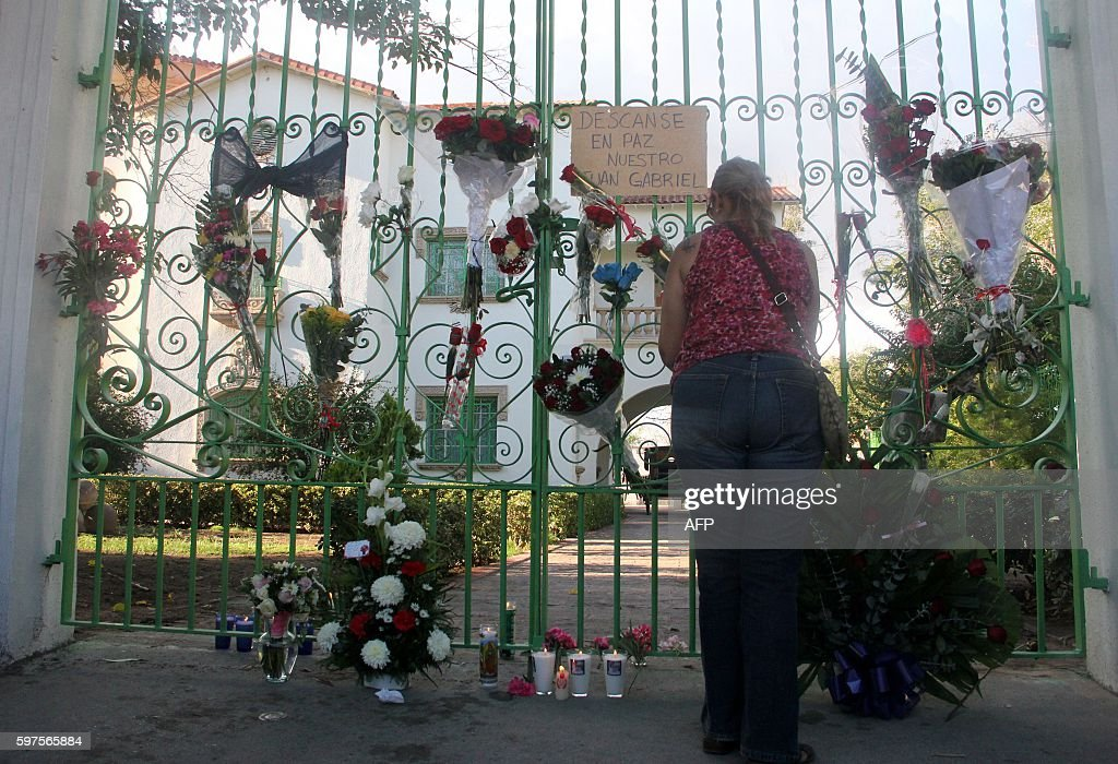 A woman puts flowers in front of the house of Mexican singer Juan Gabriel in Ciudad Juarez Mexico on August 28 2016 Mexican singer composer and...