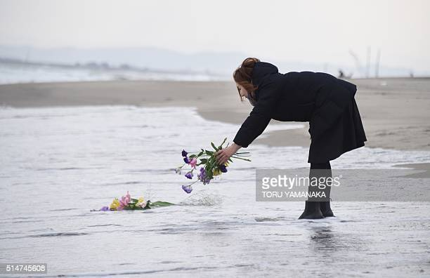 TOPSHOT A woman puts flowers into the sea to pray for victims of the 2011 earthquake and tsunami in Sendai northern Japan on March 11 2016 Japan...