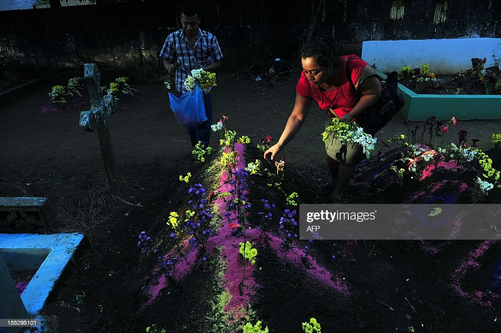 A woman puts flowers on a relative's tomb at Monimbo cemetery in Masaya, 30 km from Managua on November 2, 2012, during All Souls Day. AFP PHOTO/Hector RETAMAL