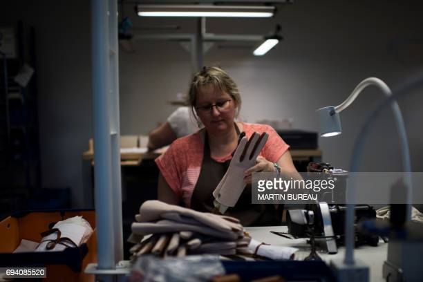 A woman puts gloves on a display stand at Hermes leather workshop on the eve of the inauguration day in SaintJunien central France on June 8 2017 /...