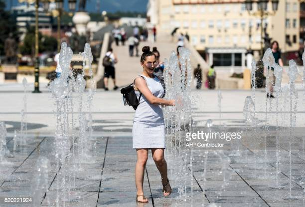 A woman puts her hands in the water of a fountain in Skopje on July 21 where temperatures reached 35 C / AFP PHOTO / Robert ATANASOVSKI
