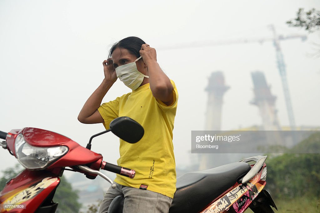 A woman puts on a mask before riding on a motorcycle in Pekanbaru, Riau Province, Indonesia on Friday, March 7, 2014. Indonesian central bank Governor Agus Martowardojo embarked on the country's most aggressive rate-increase cycle in eight years within a month of taking the helm in May to shore up the rupiah and damp price pressures. Photographer: Dimas Ardian/Bloomberg via Getty Images