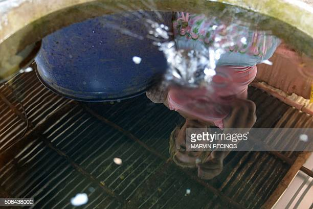 A woman puts Sambo fish in a water tank as part of a mosquito control project in the village of San Diego village in La Libertad Salvador on February...
