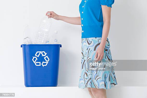 A woman putting a bottle in a recycling bin