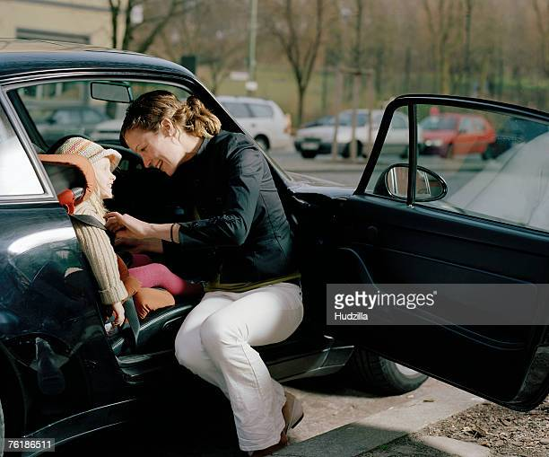 A woman putting a safety belt on her daughter