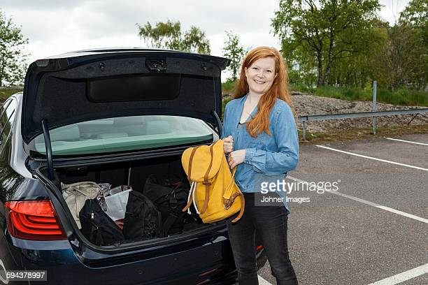 Woman putting backpack in car boot