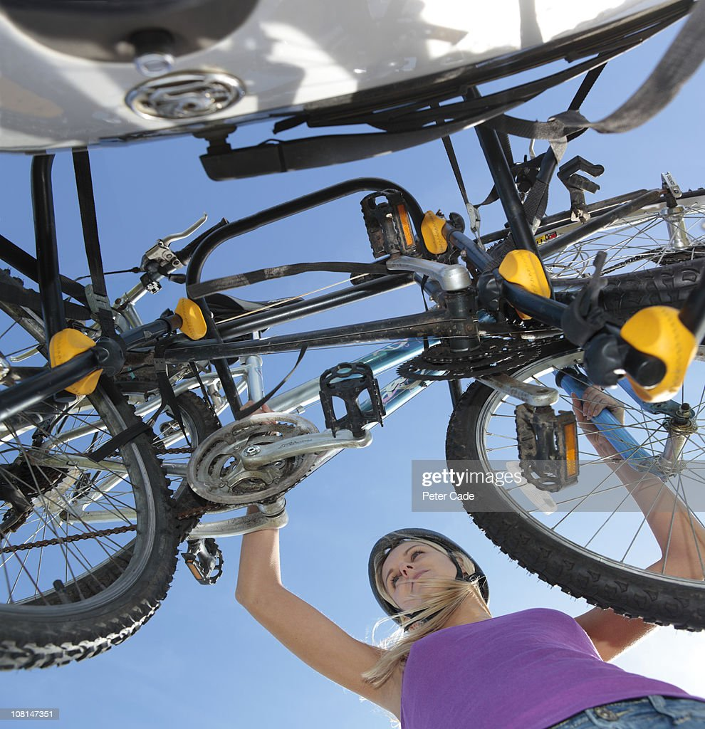 woman putting bikes onto bike rack on car : Stock Photo