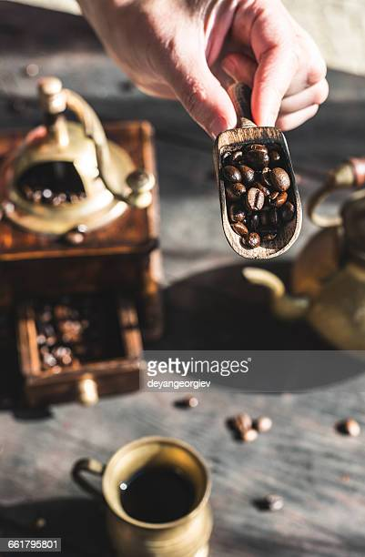 Woman putting coffee beans in vintage coffee grinder