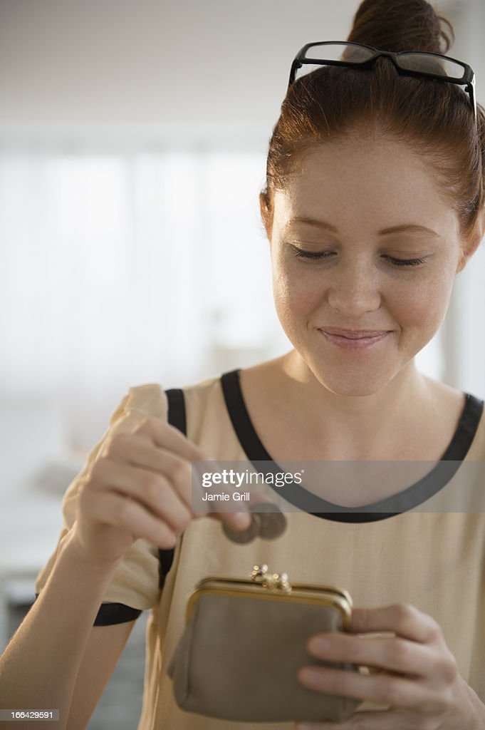 Woman putting coins in purse : Stock Photo