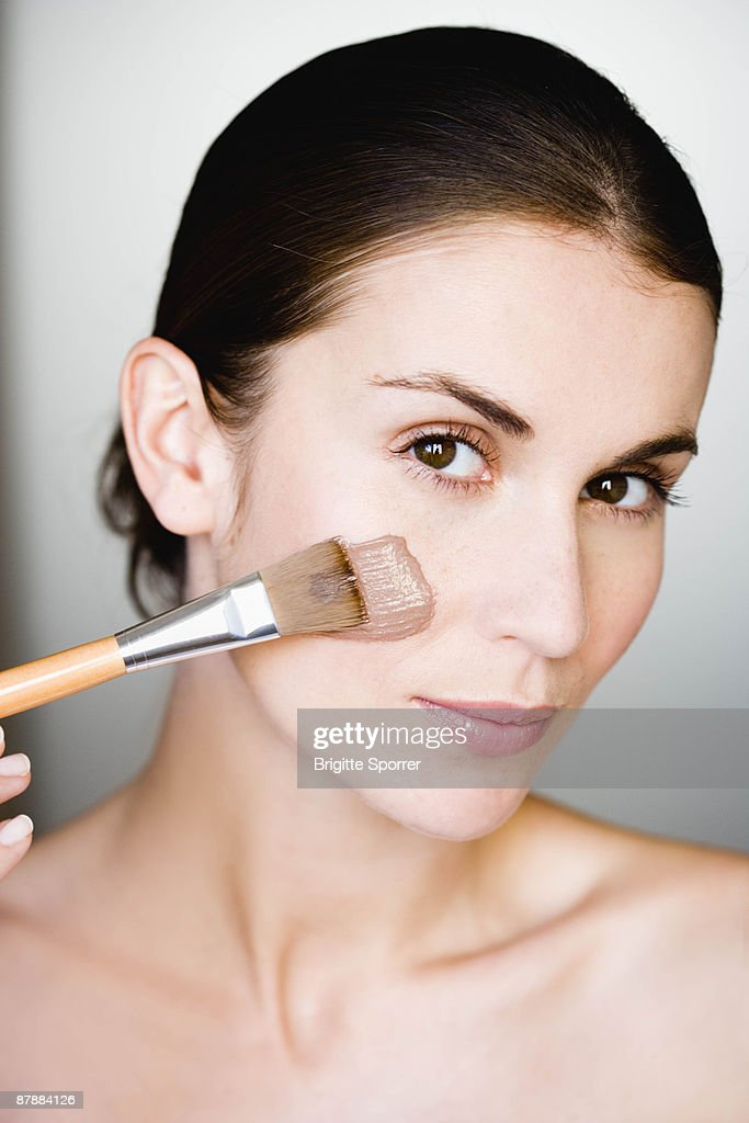 Woman putting face mask on : Stock Photo