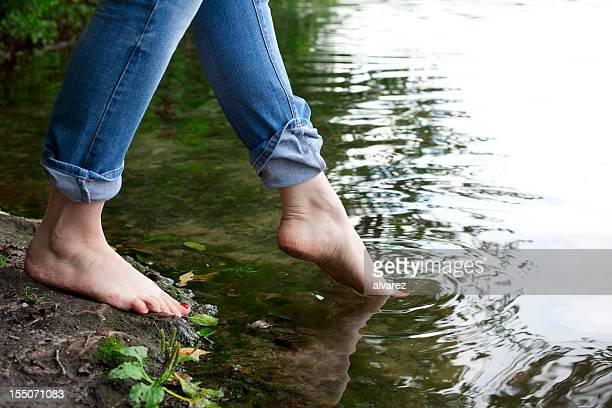Woman putting foot in lake