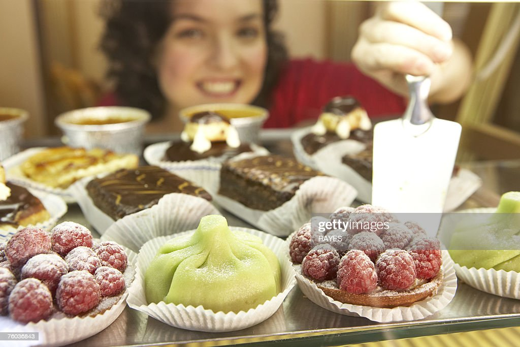 Woman putting fruit cakes on display, smiling, portrait, close-up