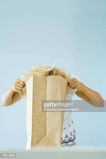 Woman putting head into paper grocery bag