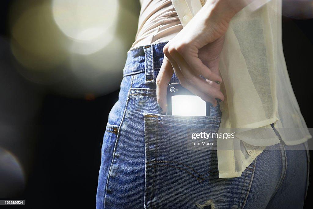 woman putting illuminated mobile into back pocket